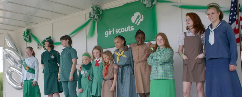 Girls in historicl Girl Scout uniforms